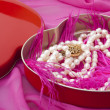 Pearls in a heart-shaped box on a pink background — Stock Photo #7382080