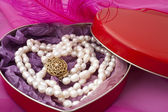Pearls in a heart-shaped box on a pink background — Stock Photo