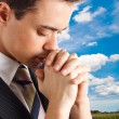 Young man praying - Stock Photo