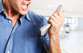 Businessman screaming at the phone — Stock Photo