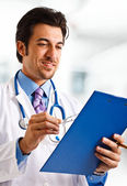 Doctor looking at a case history — Stock Photo