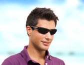 Young man smiling on the beach — Stock Photo