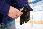 Mechanic putting safety gloves — Stock Photo