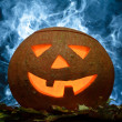 Halloween pumpkin on leafs with blue smoke - Stock Photo
