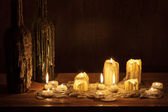 Melting candle in wooden shelf with bottle — Stok fotoğraf