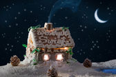 Snowy gingerbread cottage at night in winter — Stock Photo