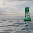 Navigational buoy in calm seas with clouds — Stock Photo