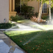 Sprinklers running onto the sidewalks of a typical American trac - Stock Photo