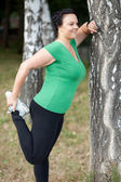 Happy overweight woman stretching in the woods — Stock Photo