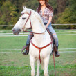 Stock Photo: Beautiful cowgirl riding white horse