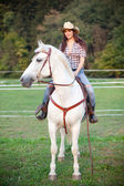 Beautiful cowgirl riding a white horse — Stock Photo