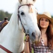Beautiful cowgirl taking her horse for a ride — Stock Photo