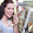Cute brunette buying cosmetics. Applying lipstick in a drugstore — Foto de Stock