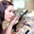 Young woman testing cosmetics. Selective focus. — Stock fotografie
