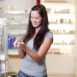 Happy young woman buying a perfume — Stock Photo #7257098