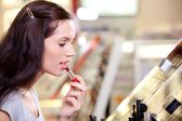 Beautiful young woman buying lipstick. Shallow DOF. — Stock Photo