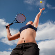 Royalty-Free Stock Photo: Young woman playing tennis, about to hit the ball. Copy space