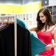 Beautiful young woman shopping in a clothing store. Shallow DOF. — Stock Photo #7323354
