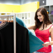 Beautiful young woman shopping in a clothing store. Shallow DOF. — Stock Photo
