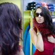 Narcissistic young woman in a clothing store - Stok fotoraf