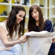 Two young women picking a dress in a clothing store - Stock Photo