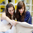 Two young women picking a dress in a clothing store — Stock Photo