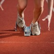 Action packed close-up image of a female athlete leaving the starting block — Stock Photo