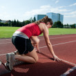 Female athlete in starting block, getting ready to go — Stock Photo #7325300