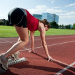 Female athlete in starting block, getting ready to go — Stock Photo #7325313