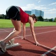 Female athlete in the starting block, getting ready to go — Stock Photo #7325313