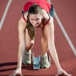 Royalty-Free Stock Photo: Young female athlete on a running track, ready to go from starting blocks