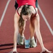 Young female athlete on a running track, ready to go from starting blocks — Stock Photo