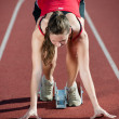 Stock Photo: Young female athlete on a running track, ready to go from starting blocks