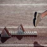 Спортсмен, оставляя начиная блоки для sprint на трек — Стоковое фото