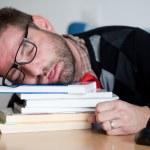 累了睡在一大堆书上的怪胎 — 图库照片