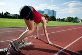Female athlete in the starting block, getting ready to go — Stock Photo