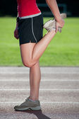 Girl stretching on a running track - side view — Stock Photo