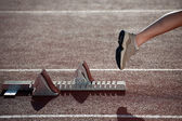 Athlete leaving the starting blocks for a sprint run on a track — Stock Photo