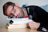 Tired geek sleeping on a bunch of books — Stock Photo