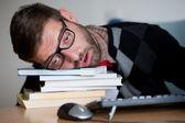 Nerd cansado dormido en un montón de libros — Foto de Stock