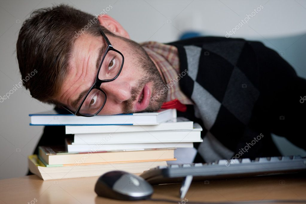 Tired nerd falling asleep on a bunch of books   Stock Photo #7329853