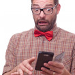 Hilarious nerd using a gadget - Stock Photo
