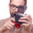 Stock Photo: Nerd enthusiastically using a gadget. Isolated on white.