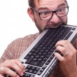 Geek hysterically biting the keyboard - Stock Photo