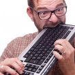 Geek hysterically biting the keyboard — Stock Photo