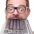 Eccentric geek biting into a keyboard - Stockfoto