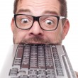 Eccentric geek biting into a keyboard - Stock Photo