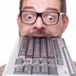 Geek biting into a keyboard - Stock Photo