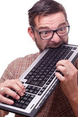 Geek hysterically biting the keyboard — Stockfoto