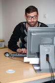 Excited nerd using the computer — Stock Photo